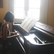 Alysta playing an old piano